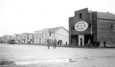Fire and Explosion February 13, 1943, The day after. 102nd Ave, facing north, looking from 11th St., 5 to $1 Store, Reliable Meat Market, Wing's Cabaret, Northern Drugs, Community Store and Lawrence Meats, all with damage. Dawson Creek , B.C., February 14, 1943