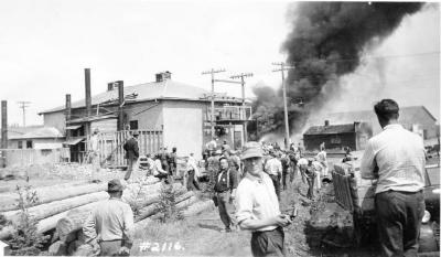 Babcock Garage fire, located 102 Ave Power house in front of the smoke. Dawson Creek , B.C., June 2, 1943