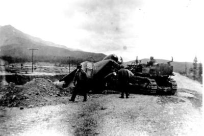 Wrecked truck with bulldozer doing a rescue Alaska Highway 1942-43