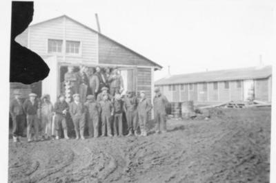 10 unidentified men standing on a muddy street in front of a building, Frank Lambert 4th from right, Dawson Creek, B.C. 1943