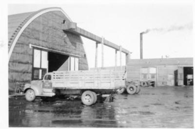 Truck parked in front of garage truck bay, Dawson Creek, B.C. 1943-44