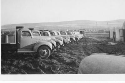 Long row of identical dump trucks, Dawson Creek, B.C. 1943-44