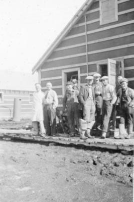 9 unidentified men standing on a wooden sidewalk, Dawson Creek, B.C. 1943-44