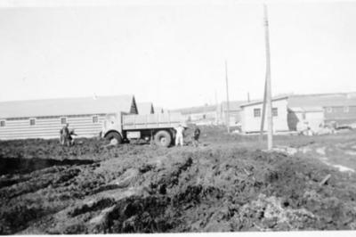 5 men attempting to free a truck stuck in the mud, Dawson Creek, B.C. 1943-44