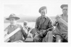 4 unidentified uniformed men in a rowboat, 2 are rowing and 2 hold fishing rods, Alaska Highway 1941-1944