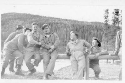 6 unidentified men in uniform sitting on a log barrier, Alaska Highway 1941-1944
