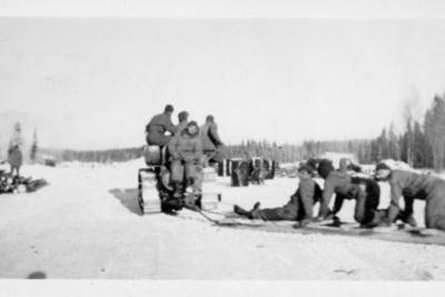 4 unidentified men on a snow tractor pulling 3 unidentified men on a skid platform, Alaska Highway 1941-1944