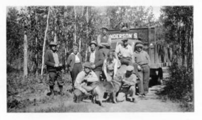 Colleen Hadwen, Evelyn Anderson, Dr. F.L. Buggins, Art Pelletier, Julius Sathers, C.M. Kennedy, Slim Anderson, Ray Hell and Ed Anderson standing in front of Anderson's Motors truck (not in order), Monkman Highway, B.C. 1938