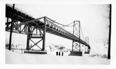 Three unidentified men standing on the ice under the Peace River Bridge at Taylor, B.C. 1938-1946