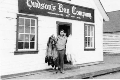 Hudson's Bay Co. Store, Unknown man holding furs, Lower Post, BC 1950