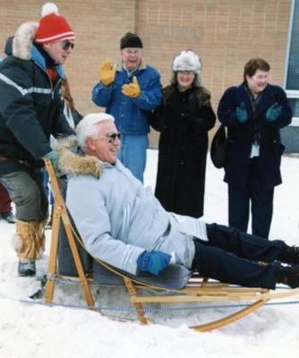 Leslie Nielsen riding in dog sled, Rendezvous '92, Dawson Creek, February 16, 1992