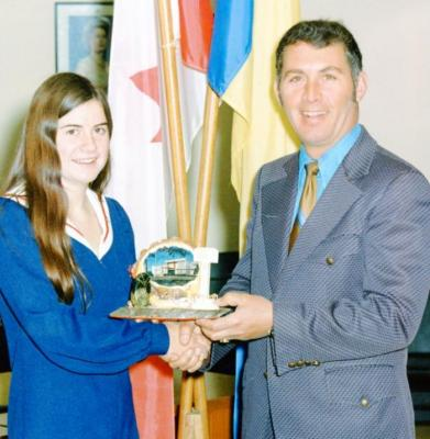 Mayor Robert Trail presenting unidentified young woman with Dawson Creek plaque, 1981-1993