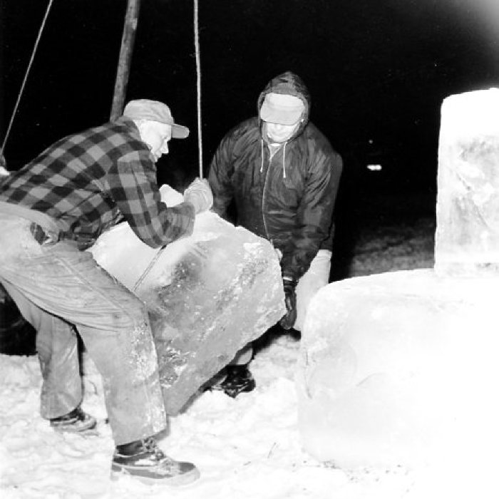 Winter Carnival, Wally Raedeke and Jim King wrestle a block of ice into place on the walls of the Ice Palace. Dawson Creek, BC February 16, 1966
